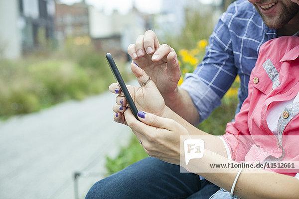 Pärchen mit Smartphone im Außenbereich