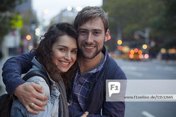 Junges Paar  das sich nachts auf der Stadtstraße umarmt  Porträt