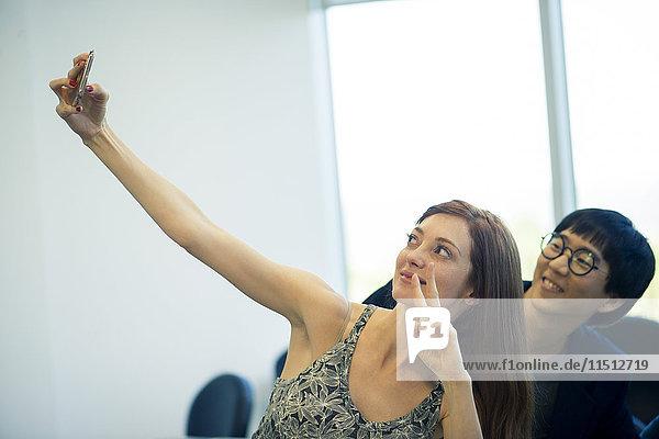 Frau  die Friedenszeichen macht  während sie Selfie mit einem Freund nimmt.