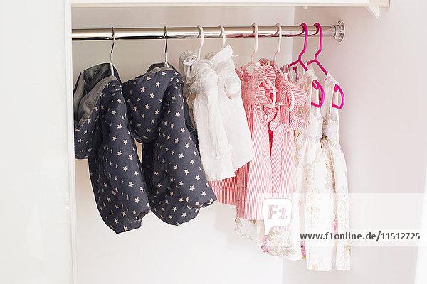 Babykleidung im Schrank hängend