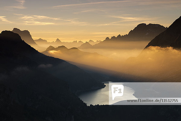 Orange light beam and mist on peaks of Dolomiti and Fedaia Pass  Cima Belvedere  Val di Fassa  Trentino-Alto Adige  Italy  Europe