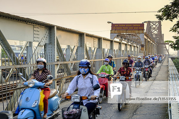 Motorbike commuters on a pedestrian pavement (sidewalk) on a railway bridge over the Red River in Hanoi  Vietnam  Indochina  Southeast Asia  Asia