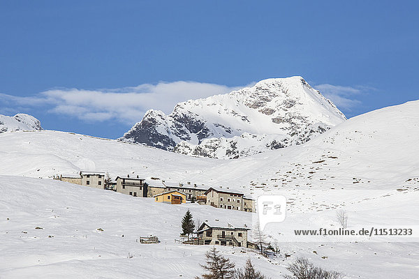 The snowy huts frame Peak Tambo in the background  Andossi  Spluga Valley  Province of Sondrio  Valtellina  Lombardy  Italy  Europe