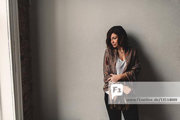 Frau stehend mit gekreuzten Armen  grauer Wandhintergrund