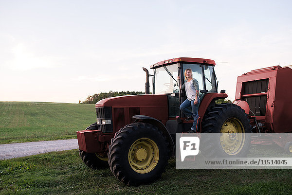 Portrait of woman standing on tractor