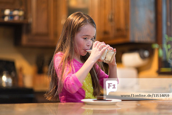 Young girl drinking milk at kitchen table