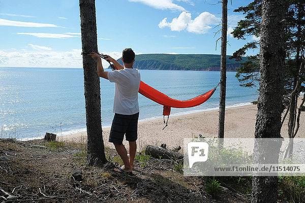 Man preparing hammock  Ingonish  Cape Breton  Nova Scotia  Canada