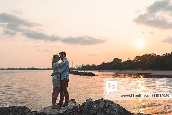 Romantic couple face to face on boulder  Lake Ontario  Toronto  Canada