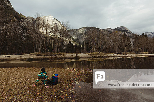 Male hiker sitting by lake looking out at landscape  Yosemite National Park  California  USA