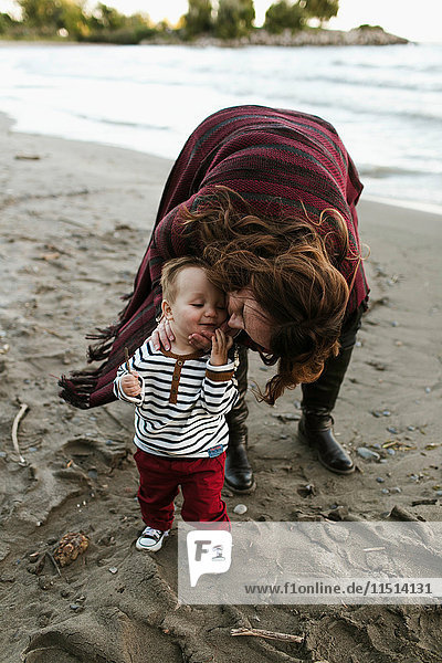 Mother on beach kissing baby boy on cheek  Toronto  Ontario  Canada