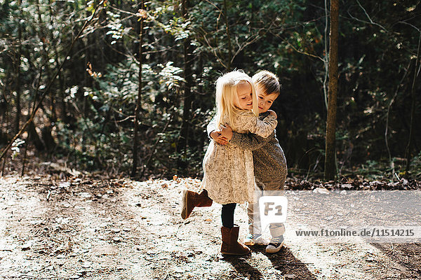 Siblings hugging and playing on gravel road