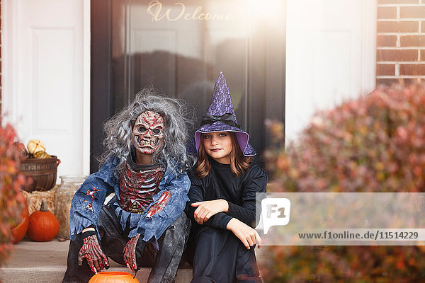 Friends dressed as witch and zombie  sitting on front step of home