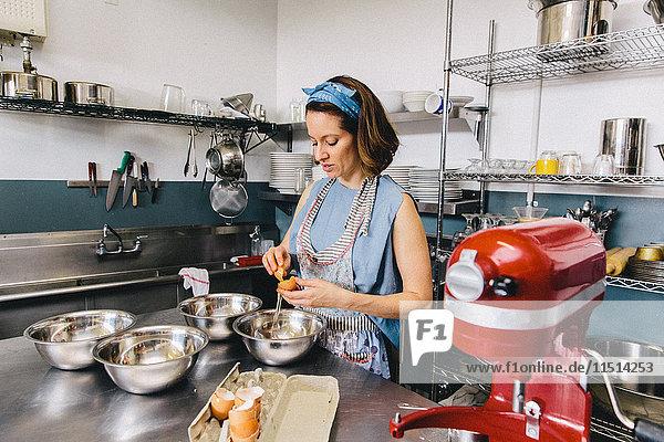 Frau bricht Ei in Rührschüssel