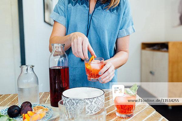 Frau bereitet Cocktail zu