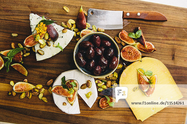 Variety cheese plate with figs  olives  pistachios  cleaver on wooden chopping board