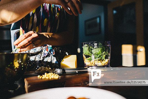Frau bereitet Nudeln mit Basilikum  Pinienkernen zu