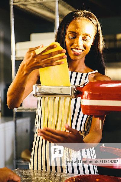 Student flattening dough with pasta maker