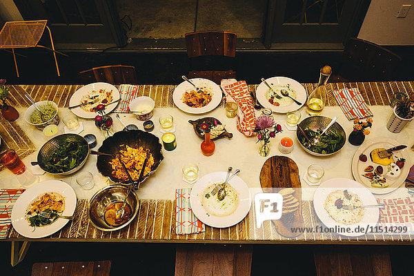 Gedeckter Esstisch für sechs Personen  mit verschiedenen Gerichten