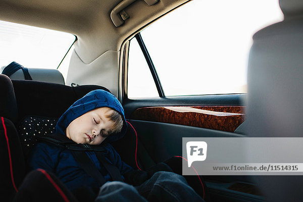 Young boy sleeping in back seat of car