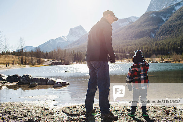 Grandfather and grandson beside river  rear view  Rocky Mountains  Canmore  Alberta  Canada