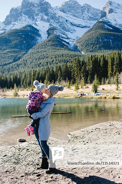 Mother holding and kissing daughter beside river  Three Sisters  Rocky Mountains  Canmore  Alberta  Canada