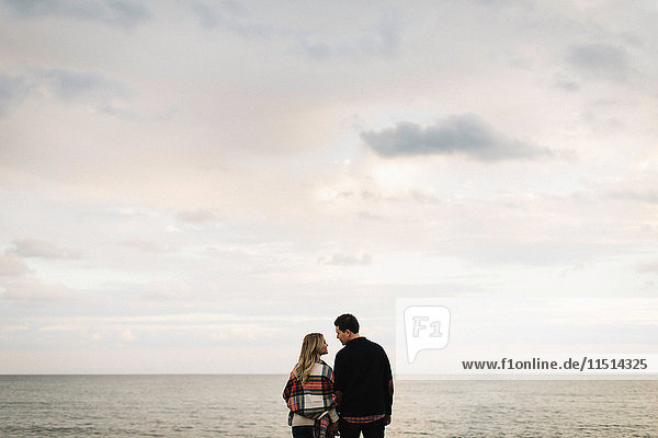 Young couple outdoors  beside sea  rear view