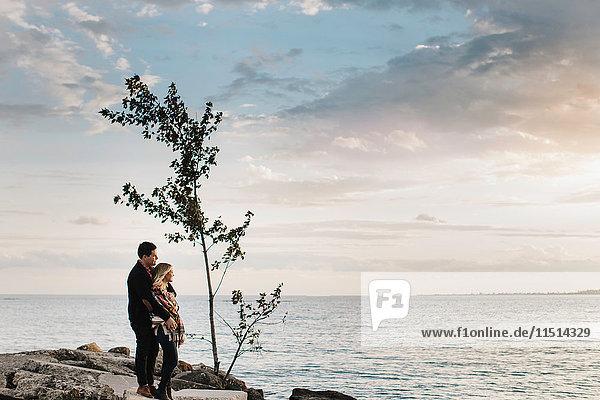 Junges Paar steht auf Felsen am Meer und schaut auf die Aussicht