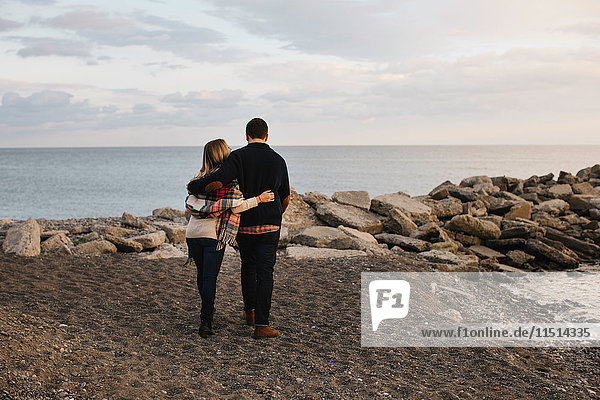 Young couple standing beside sea  rear view