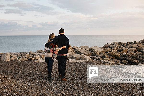 Junges Paar am Meer stehend  Rückansicht