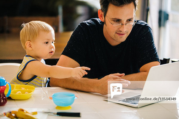 Father and young son sitting at table  father using laptop  son pointing at screen