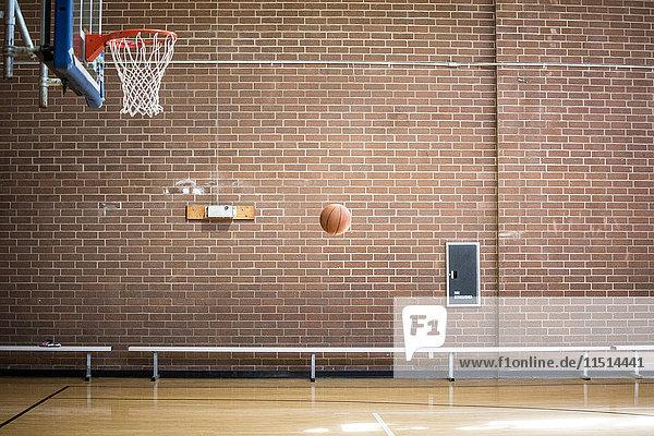 Basketballball mitten in der Luft auf leerem Basketballfeld