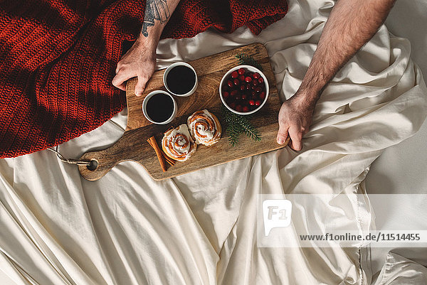 Overhead view of male hands holding breakfast for two in bed