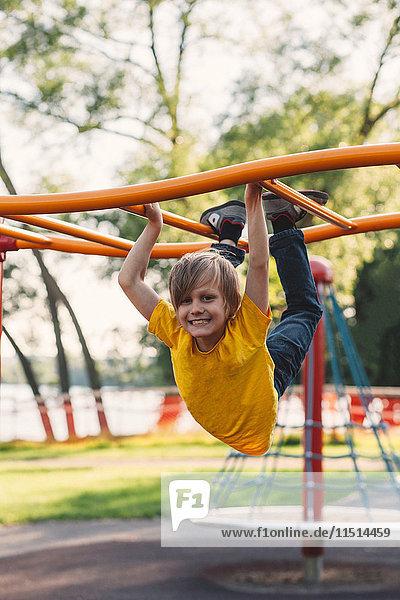 Porträt eines Jungen  der am Klettergerüst des Parks hängt