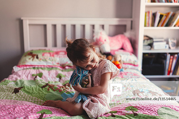 Girl sitting on bed hugging rag doll