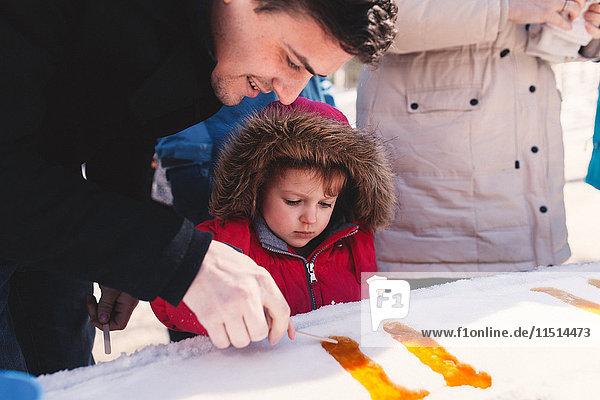 Girl in fur hood with father making lolly in snow ice