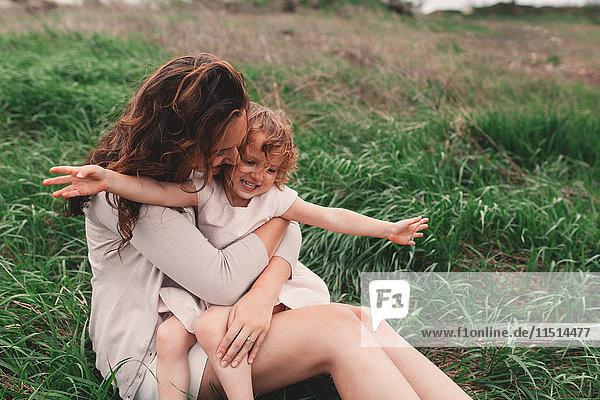 Mädchen sitzt auf dem Schoss der Mutter auf windigem Feld
