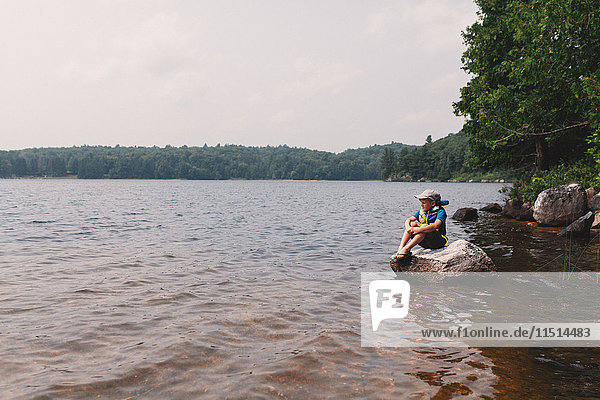 Boy sitting on rock at the edge of a lake