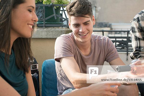 Junge erwachsene Freunde entspannen bei Dachterrassenparty