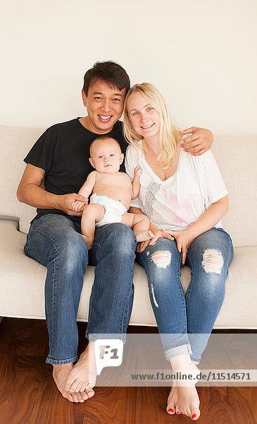 Porträt von auf dem Sofa sitzenden Eltern mit dem kleinen Sohn