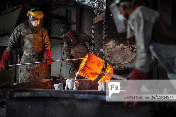Metallarbeiter in der Gießerei  die geschmolzene Bronze gießen