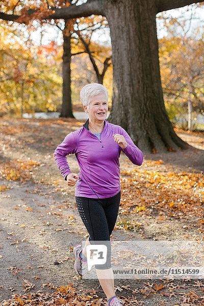 Ältere Frau trainiert  läuft  in ländlicher Umgebung