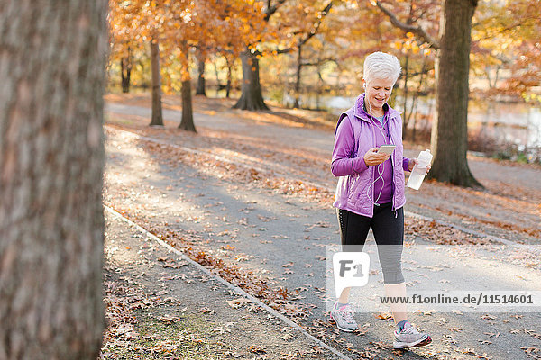 Senior woman walking outdoors  using smartphone  wearing earphones and holding water bottle