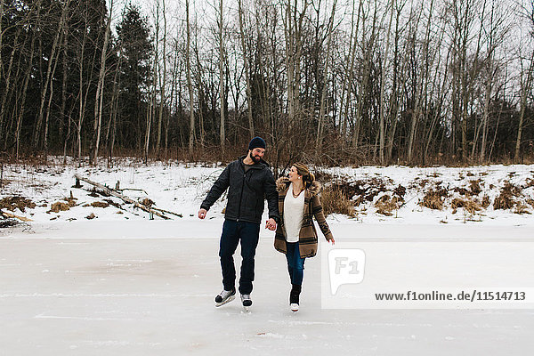 Couple skating on frozen lake  Whitby  Ontario  Canada
