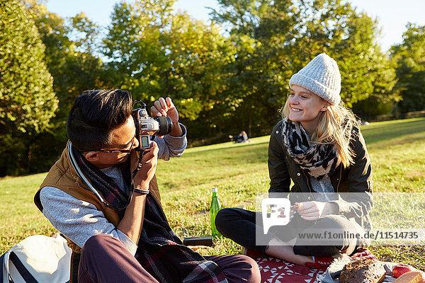 Mittelgroßer erwachsener Mann fotografiert seine Freundin beim Picknick im Park