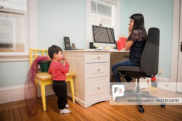 Männliche Kleinkinder essen Cookie  während Mutter mit Laptop