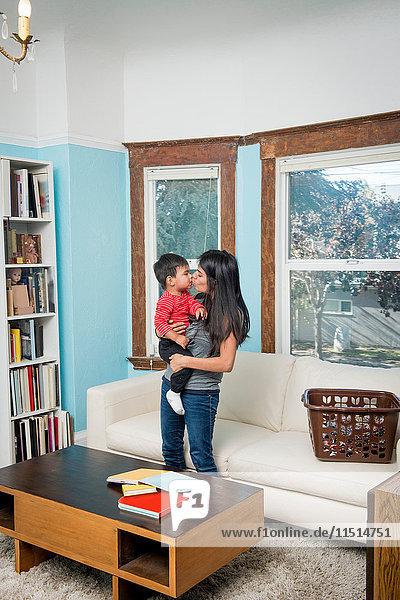 Frau küsst mit Kleinkind Sohn im Wohnzimmer