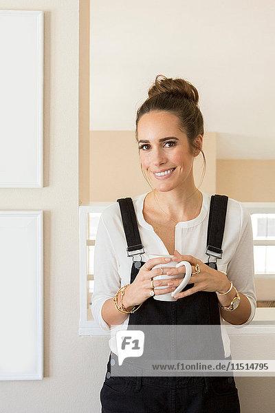 Portrait der schönen weiblichen Mode und Lifestyle-Bloggerin mit Kaffeetasse