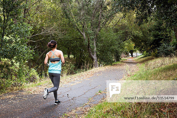 Rückansicht einer Läuferin  die im Park läuft
