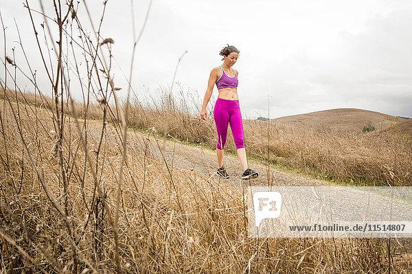 Mid adult woman training  walking on dirt track