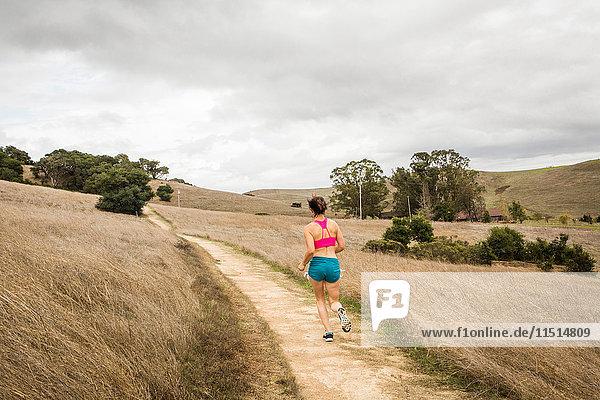Rear view of female runner running on dirt track in landscape